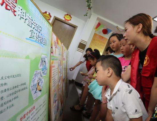 8月9日,在肥东县店埠镇镇南社区,志愿者带领孩子学习地震科普知识.